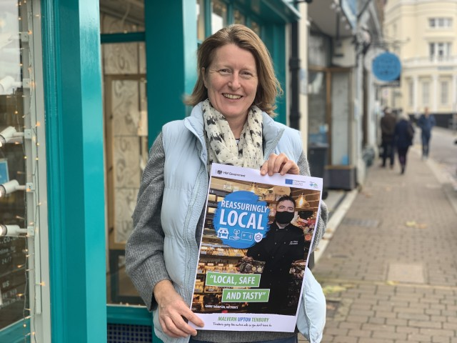A photo of Councillor Sarah Rouse standing outside a shop in Great Malvern holding a Reassuringly Local campaign poster.